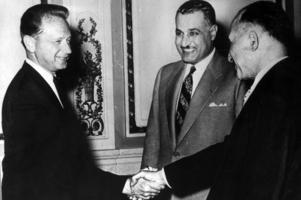 Arkiv - odaterad: FN:s generalsekreterare Dag Hammarskjöld (tv) och Egyptens president Gamal Abdel Nasser (mitten). Hammarskjöld skakar hand med en ej namngiven man.