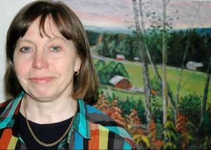 Uppväxten i Tångeråsen, Offerdal, som ses på tavlan bakom Eira Kunze Nilsson, har inspirerat hennes vardagsrealistiska diktskrivande på jamska om människor och människoöden.