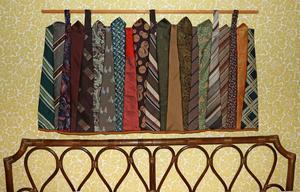 Ovanför sängen hänger denna lite annorlunda rana som Birgitta gjort av ihopsydda slipsar.