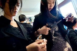Antivåldskampanj och insamling. Studiekamraterna Hu Lan och Yishen Yang gör vita bandet-dekorationer.