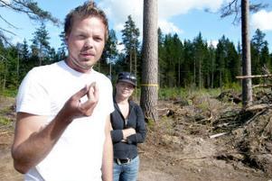 Erik Johansson håller upp en grönsten. I bakgrunden står Anna Ingvarsdotter som i dag är extra glad att ha en arkeolog till bror.
