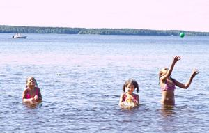Tvillingarna Alicia och Olivia Larsson badar med storasyster Felicia Aronsson på Strandbaden, nära det otjänliga vattnet.
