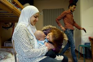 Zahraa har kommit från skolan och pussar på lillebror Hamza som sitter i mamma Rana Dabits knä. I bakgrunden syns pappa Moataz Amino.