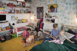 Rio, Ali och Billie leker på golvet i barnrummet. I sängen sitter Folke med Neneh.