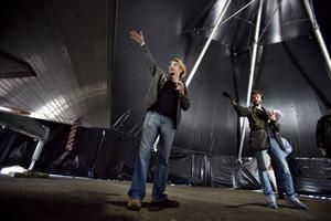 Krister Lindgren berättar för lokalradions reporter och andra hur tältet fälls ner i trailern genom det uppfällbara taket.