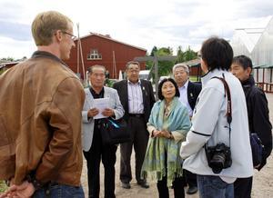Närmast kameran Loman Lars Eriksson och tolken Stefan Mori berättar om skolans trädgårdsdel för intresserade japaner.