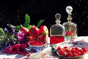 Frukt och bär odlades och togs om hand i trädgården. Frukterna på bilden är placerade på ett av Karins vävda sängöverkast där hon knutit in mönster av en majstång och blommor.
