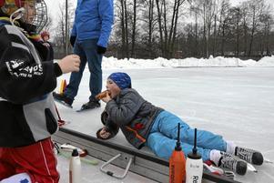 Korv och skridskor. Erik Bäckman tar en paus i åkandet för att få någonting i magen. Bredvid gör sig Ronja Lindh klar för isen.