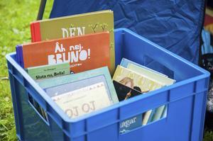 Åsa Ramsell har hela lådan full med böcker som barnen får låna och läsa för hunden Alwin.    – Vi vill motivera barn till att läsa och göra det till en mysig stund med hunden och den dömer inte någon om den skulle läsa fel, säger Åsa.