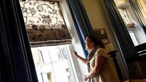 Att hänga gardiner är en konst - här får du alla tipsen. Delägaren Marika Pehmüller hissar en gardin i fönstret på Gardinmagasinet.