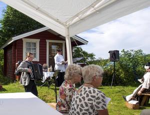 David Wahlén spelar till psalmsången. I bakgrunden kyrkoherde Camilla Nordström.