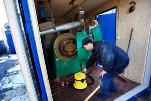 """Stig Linder visar pelletspressen som står i en container.  """"Den anlände i dag. Nu ska vi bygga ett skjul här bredvid som pressad pellets ska transporteras till från pressen"""", säger han.  Foto: Håkan Luthman"""