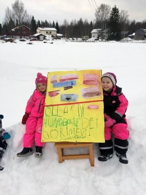Julia Matsson och Hilma Lilja visar förskolans skylt med hundbajspåsarna.