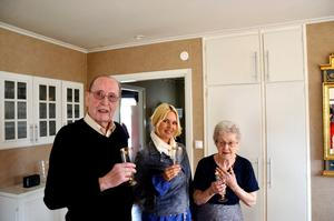Inghe-Lars Bäck firar vinsten med ett glas bubbel tillsammans med hustrun Alice och vinstutdelaren Magdalena Graaf.