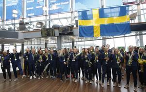 De svenska fotbollsdamerna fick ett varmt välkomnande på Arlanda. Rakt under det blå fältet till vänster på den svenska flaggan står Hanne Gråhns från Hedemora med sin OS-silvermedalj .