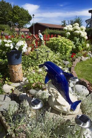 Lekfullt. Bland växter som hortensia, petunia, ormbundkar och kärleksört gömmer sig prydnadsföremål.