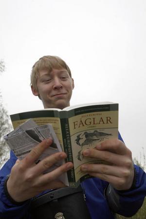 Andreas Edström studerar fågelboken.