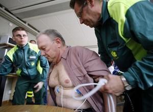 Det gäller att hålla ner hjärtverksamheten så mycket som möjligt när det finns misstankar om hjärtinfarkt. Ambulanspersonalen lyfter Stig så att han inte behöver anstränga sig.