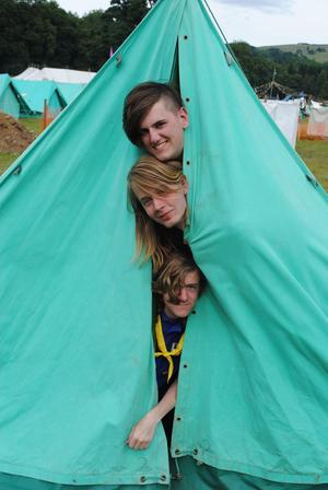 Pontus Hassis, Otto Tysklind och Craig Whitelaw tittar ut ifrån tältet de bor i tillsammans med flera andra scouter.