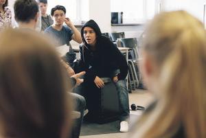 Oldoz Javidi spelar både elev och lärare. Scenografin består av bara ett par klossar och en matta.