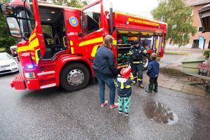 Brandmännen öppnade brandbilarna och satte på blåljusen, till de besökande barnens (och kanske också vuxnas) stora förtjusning. André Pettersson får en guidning i hur en brandman måste klä sig för att skydda sig mot elden.
