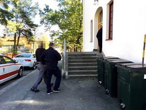 Mannen är häktad och fördes in i Hudiksvalls tingsrätt av Kriminalvårdens personal.