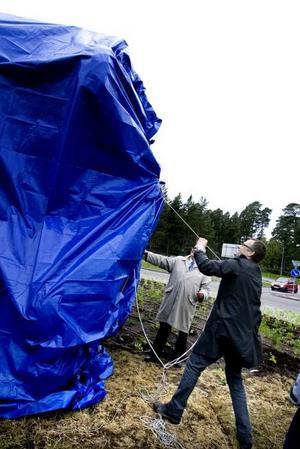 AVTÄCKNING. Konstnären Ingo Vetter och Mats Öström, ordförande i kultur- och fritidsförvaltningen, hugger i för att avtäcka skulpturen.