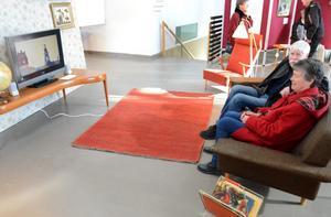 Björnjägarn på tv. Ulf och Inger Hedenäs i tv-soffan. En tecknad film med Björnjägarns figurer visas på tv.