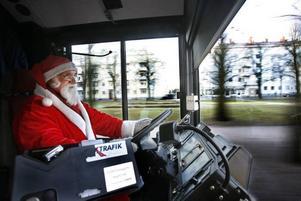 Tomten kör bussen med säker hand trots att han greppar ratten med lovikkavantar.