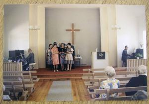 Sånggrupp framträder på scenen i missionshuset.