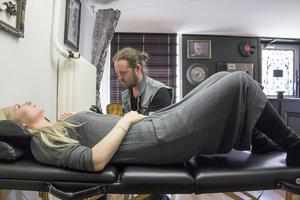 Mattias Österberg tatuerar Cizzi Bergqvist som även hon hjälper till att bidra till insamlingen.