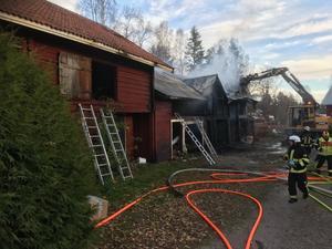 Det är en del av en ladugårdslänga som brunnit, och här rivs den delen ner för att brandkåren ska kunna släcka branden ordentligt.
