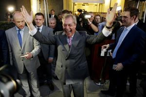 Nigel Farage, the leader of the UK Independence Party celebrates and poses for photographers as he leaves a
