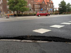 Mot Ahlbergshallen har asfalten brutits upp mot trottoarkanten.