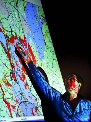 Jan Lundström, projektledare, visar vilka områden som bekämpats och vilka som inte har det.