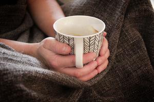 Josefine kurar under en filt och vrider en kaffekopp mellan sina händer.