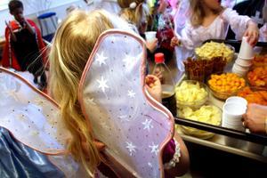 En ängel med stora vingar väntar på att bli serverad snacks och dricka.