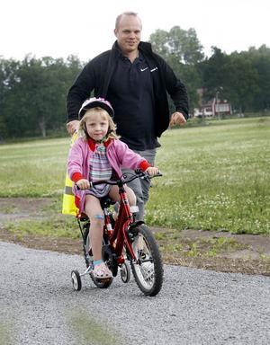 Full fart. Astrid Jansson, 4 år, var bland de första att ge sig ut på den nya cykelleden. Pappa Per Jakobsson får springa bredvid.