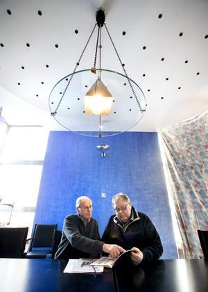 Konferensrummet i gamla riksbankshuset. Ägaren Stieg Ekström och Håkan Johansson, som arbetar med att se till huset, tittar på gamla artiklar. I taket hänger en lampa speciellt designad för rummet som har koboltblå väggar och ett ventilationssystem i form av en mängd små hål i taket.