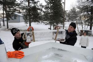 Tommy Nilsson och John Persson lyfter ett tungt isblock.