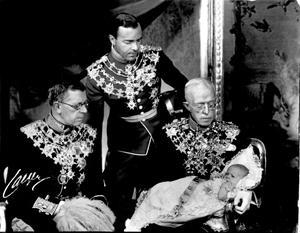 Prins Carl Gustaf (Carl XVI Gustaf) i dopklänning i armarna på sin gammelfarfar kung Gustaf V. Blivande kung Gustaf VI (t.v.) och stående prinsens far Gustaf Adolf.