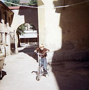 SAKNAD BAKGÅRD. Svarvare Walls son Lennart, här i tioårsåldern, inne på gården i kvarteret Kärrlandet där svarveriet låg. Lennart Wall saknar Kärrlandets gamla hus och tycker att det nya affärskomplexet stal en alltför stor del av Stortorget.