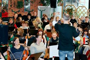 Janne Lundqvist dirigerar den stora Queenorkestern i Sjöängsskolans matsal.