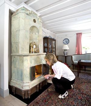 Vardagsrummets kakelugn från 1700-talet var tvungen att plockas ner helt för att den skulle gå att använda. Men i dag kan Kerstin elda i den. Lägg märke till de tidstypiska träfötterna.