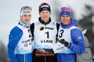 Teodor Peterson, Oskar Svensson och Nikita Kriukov på prispallen efter sprintfinalen under Sverigepremiären i skidor. Foto: Ulf Palm/TT