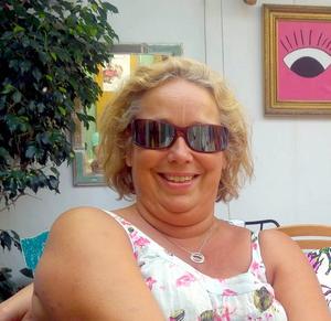 Lena Falk, förskolechefen som sadlade om. I bakgrunden Carolines tavlor.