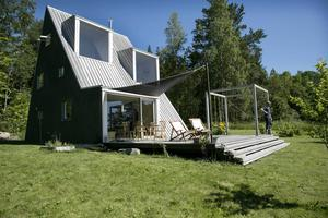 Fasaden är klädd med furupanel, tak, terrass och glaspartier i kärnfuru – allt är behandlat med pigmenterad Sioo träskydd och olja. Alla dörrar och fönster i huset är olika och köpta på Blocket.