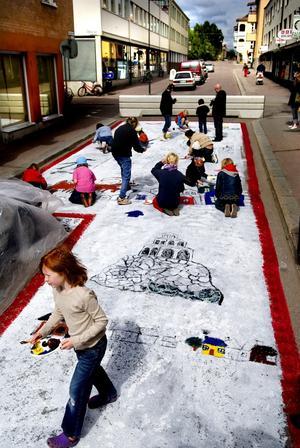 Målar asfalt. Tilda Hjelm och många andra Faluungdomar målar Slaggatans asfalt. Men redan i dag kan konsten vara borta.
