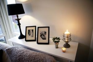 Extra yta för viktiga ting. Bakom soffan står ett sideboard som rymmer såväl belysning och fotografier som en vacker grupp med stämningsljus
