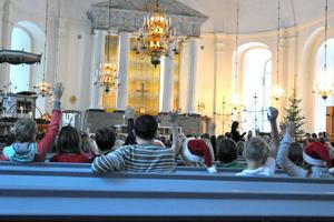 Handuppräckningar förekommer inte bara i skolan utan även i kyrkan. Eleverna räckte upp handen för att få svara när kyrkoherden Susanne Håkansson undrade om de kände till varför vi firar jul.